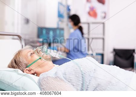 Elderly Woman Having Respiratory Disease Because Of Covid19 With Oxygen Mask. Patient In Hospital Ro