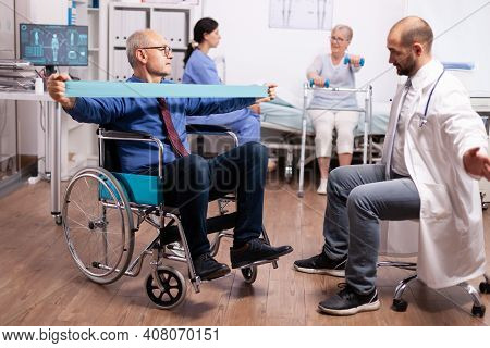 Pensioner In Wheelchair Doing Treatment With Elastic Band With Help From Medical Staff. Elderly Inva
