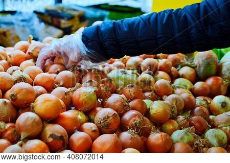 Shopper Hand On Yellow Onions In Supermarket. Yellow Onions Grocery Store Close Up. Golden Onions Bi