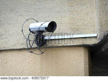 Security camera covered entangled in barbed wire mounted on the rough house wall in the in a disadvantaged district side view close up