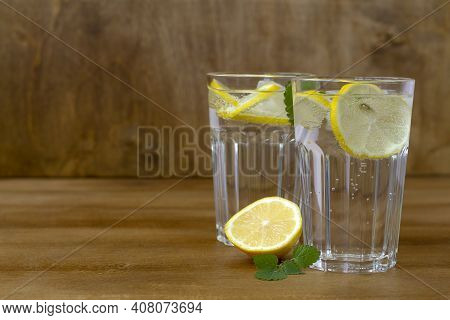 Glass Of Water With Lemon. Homemade Cold Refreshing Drink Or Water With Ice On Rustic Wood Backgroun
