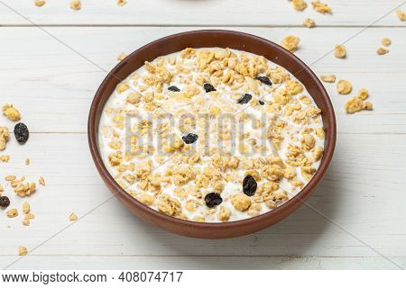 Healthy Breakfast. Muesli With Dried Grapes Is Poured With Milk In A Clay Bowl On A White Wooden Tab
