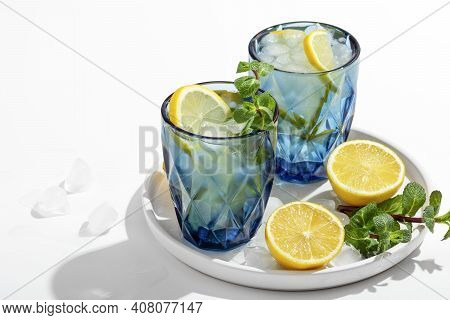 Summer Lemonade With Mint And Ice In Blue Glasses On A White Table On A Plate, Next To Lemons, Ice A