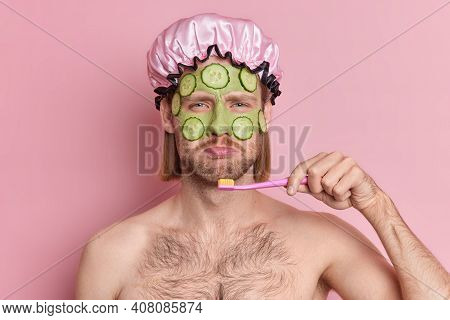 Displeased Man Applies Green Nourishing Mask On Face With Cucumber Slices To Rejuvenate Skin Looks S