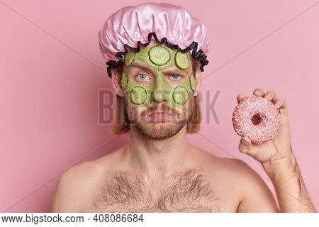 Portrait Of Displeased Sullen Man With Mustache Frowns Face Holds Delicious Donut Stands Topless Ind