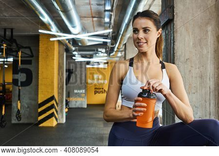 Sporty Beauty. Portrait Of A Young Cheerful Beautiful Fitness Woman In Sportswear Holding Bottle Of