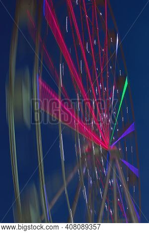 Carnival Ride Showing A Spinning Ferris Wheel In Action- Long Exposure Shot.