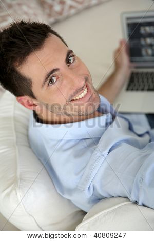 Upper view of young man using laptop computer at home