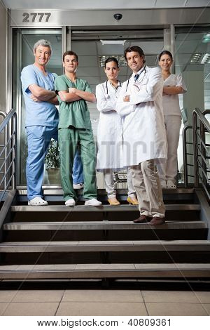 Full length portrait of confident multiethnic medical professionals standing together with arms crossed