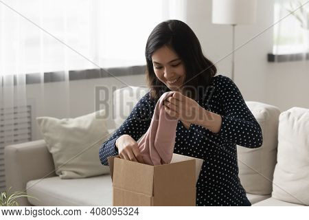 Happy Asian Female Customer Unpack Parcel Ordered At Fashion Boutique