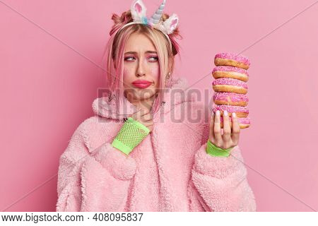Upset Blonde Woman With Bright Makeup Looks Sadly At Pile Of Delicious Doughnuts Feels Temptation To