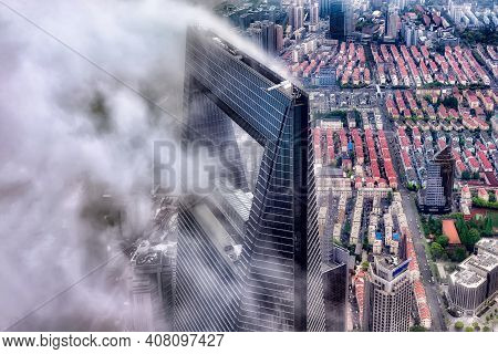 Shanghai, China - April 20, 2019: View Of Shanghai World Financial Center Emerging From Clouds. The