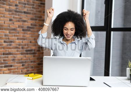 Happy Young Multiracial Student Hands Up, In Front Of The Computer, With Wide Smile, Celebrating Her