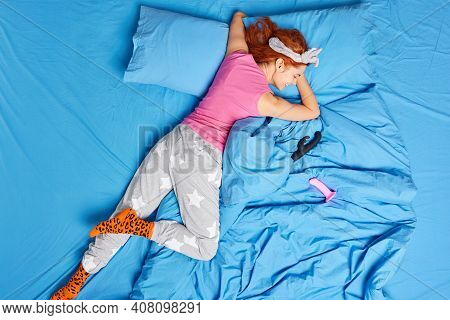 Pleased Redhead Young European Woman Lying On Stomach In Casual Pajama Satisfies Herself With Dildo