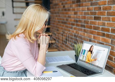Diligent Middle-aged Blonde Woman Sitting At The Laptop, Listening To The Online English Lesson, Wri