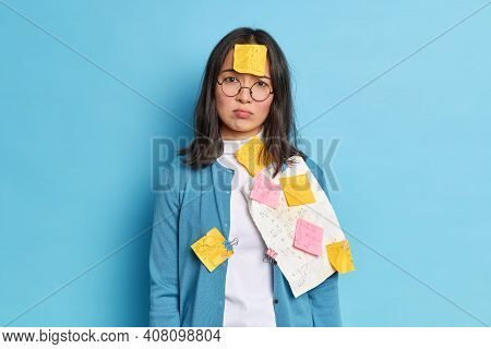 Frustrated Asian Female Office Worker Has Much Paper Work Stuck With Reminding Stickers Wears Round