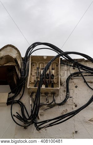 An Open Electrical Fuse Box And Distributor With Many Cables Leading In And Out In An Unsafe And Hap