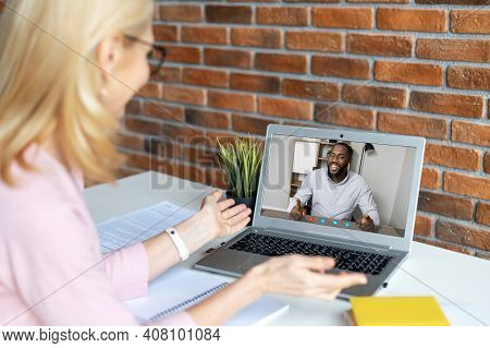 Smiling Blonde Woman With Black Glasses Talking To African American Man Friend During A Break From W