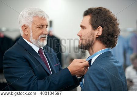 Close Up Of Senior Man Clothier Measuring Handsome Young Client In Store. Concept Of Picking Suit Fo