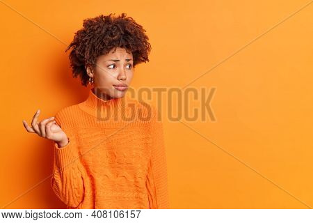 Troubled Unsure Dark Skinned Woman With Curly Hair Raises Hand Tries To Solve Problem Looks Perplexe
