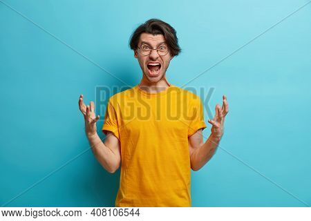 People And Irritation Concept. Annoyed European Man Gestures Angrily And Shouts Loudly Expresses Rag