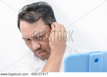 Asian Middle Man Using Tweezers To Pluck His Gray Hair Isolated On White Background, Health Care Con