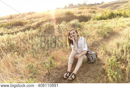 Young Brunette Female Traveler Sitting On Grass On Hill And Admiring Amazing Scenery During Sundown