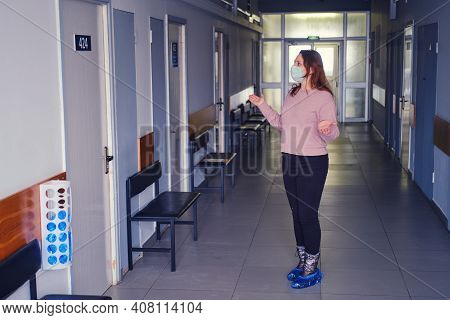 A Woman In A Face Mask Stands In The Corridor Of An Empty Clinic Without People, The Concept Of Pati