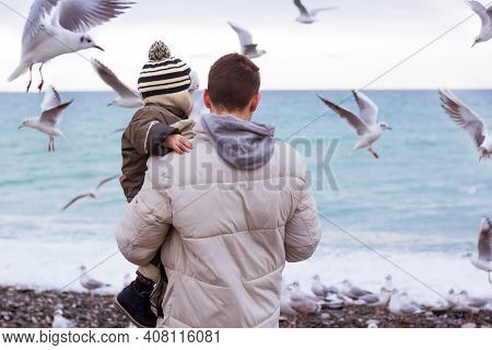 Father Holding His Son And Feeding Seagulls At The Beach. Family Time On The Seaside. Man With Boy F