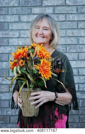 Mature Female Blond Senior  Holding Colorful Flowers In Her Hands.