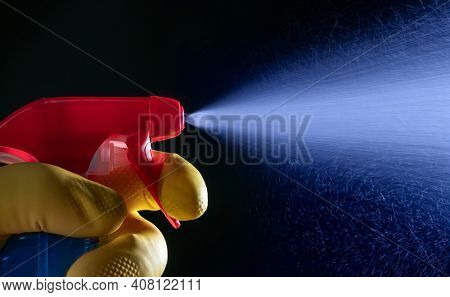 Hand with a spray bottle on a dark background