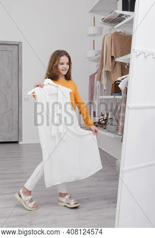 1 A White Teenage Girl 10 Years Old Holds White Dress In Her Hands And Looks At Herself In The Mirro