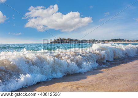 Blue wave on the beach. Blur background and sunlight spots. Dramatic natural background.