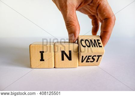 Invest Or Income Symbol. Businessman Turns A Wooden Cube And Changes The Word 'invest' To 'income'.