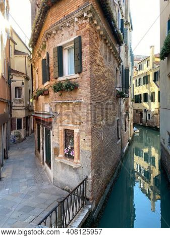 Venice, Italy, February, 13, 2021 - house corner between street and canal in Venice