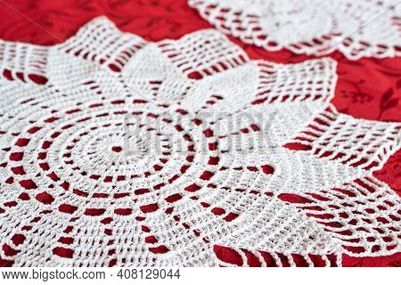 White Knitted Lace Doilies Lie On The Red Tablecloth