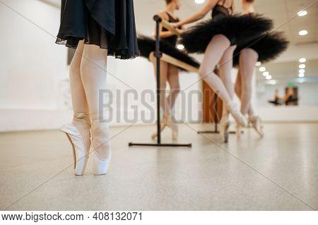 Three young ballerinas, teens rehearsal at barre
