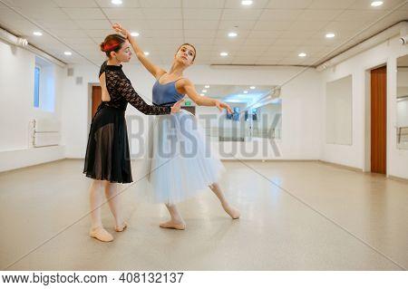 Choreographer works with young ballerina in class