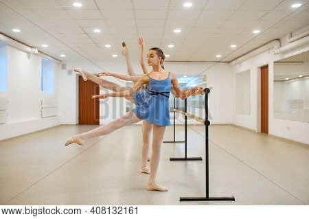 Three young ballerinas rehearsing at the barre