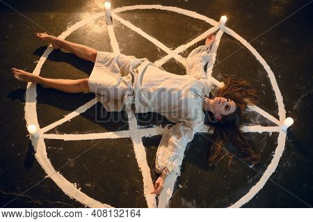 Demonic woman lying in magic circle with candles