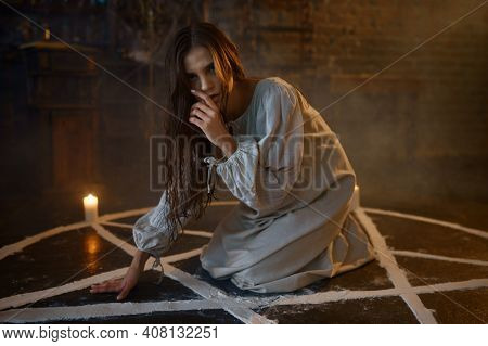 Scary demonic woman sitting in the magic circle