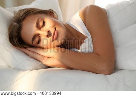 Beautiful Young Woman Sleeping While Lying In Bed Comfortably And Blissfully. Sunbeam Dawn On Her Fa