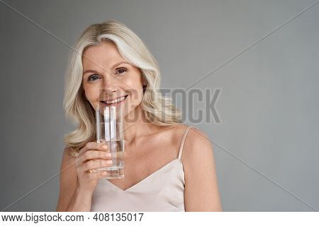Smiling Healthy Thirsty Fit Mid Aged 50s Woman Holding Glass Drinking Water. Happy Mature Lady Hydra