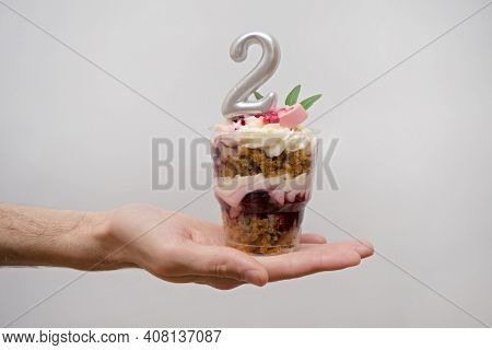 Birthday Trifle Cake With Candle Labeled Number 2 In Hand On White Background. Portioned Mini Cake