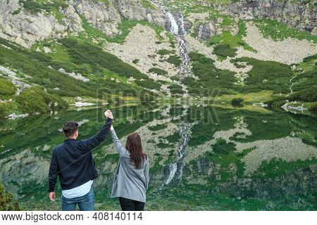 Heterosexual Couple Holding Hands Against Amazing View Of Waterfall And Lake With Transparent Clear