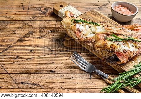 Grilled Red Seabass On A Cutting Board. Wooden Background. Top View. Copy Space