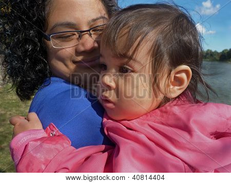 Young mother and infant daughter outdoors.