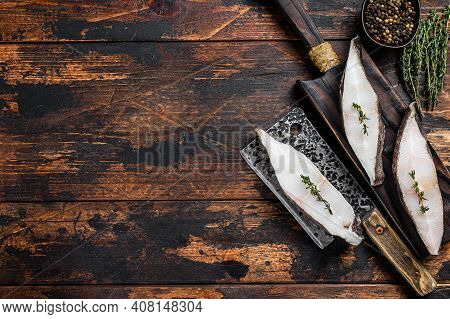 Raw Fresh Halibut Fish Steak On A Wooden Cutiing Board. Black Background. Top View. Copy Space