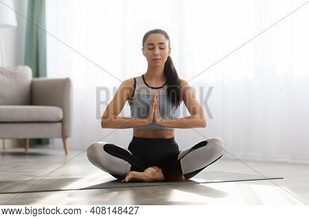 Peaceful Sporty Lady Meditating At Home, Sitting In Lotus Position With Closed Eyes, Living Room Int