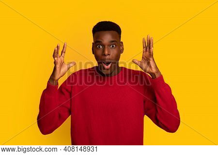 Wow. Portraif Of Amazed African American Guy Raising Hands With Excitement, Emotionally Reacting To